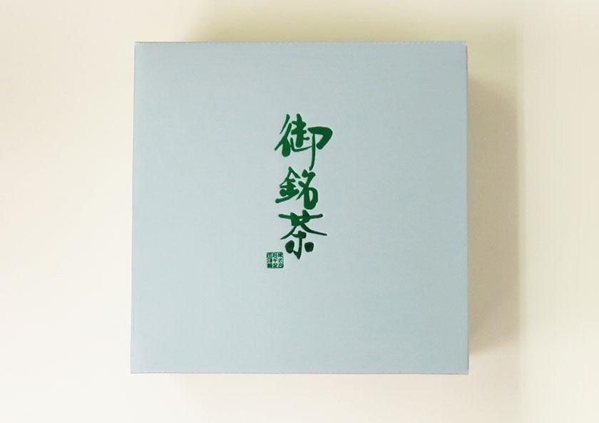 落ち着いた色合いの箱に、鮮やかな緑色の箔押しデザインの高級ギフト箱